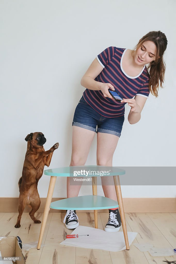 Woman taking a photo of her finished flatpack furniture