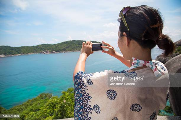 Woman taking a photo of ocean with a smartphone