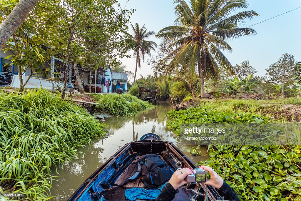 Woman taking a photo while canoeing in a small river in the forest of Mekong Delta, Vietnam