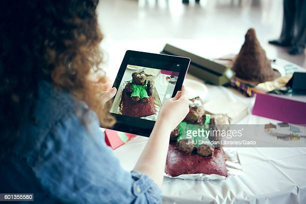A woman taking a picture of a cake decorated for 'Corduroy' by Don Freeman with an ipad at the Edible Book Festival at Johns Hopkins University...
