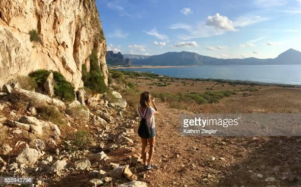 Woman taking a picture of coastline near San Vito lo Capo, Sicily