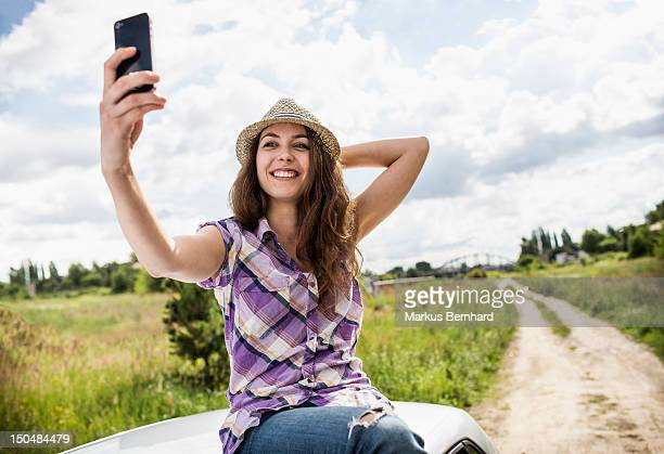 Woman taking a picture of her self on top of car.