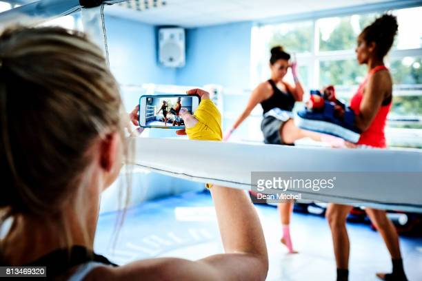 Woman taking a picture of kickboxing training