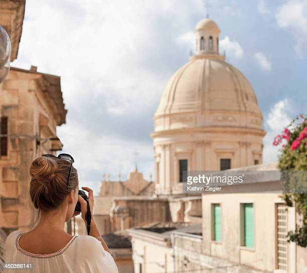 woman taking a picture of Noto Cathedral, Sicily