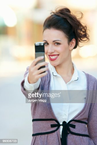 A woman taking a picture on her mobile : Stock Photo
