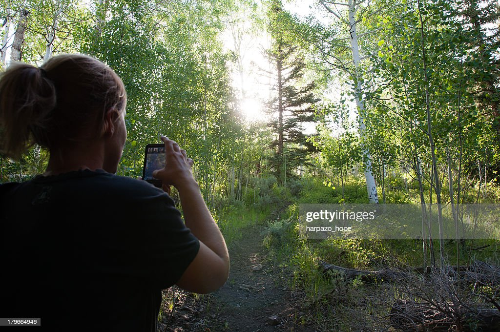 Woman taking a picture with her camera phone. : Stock Photo