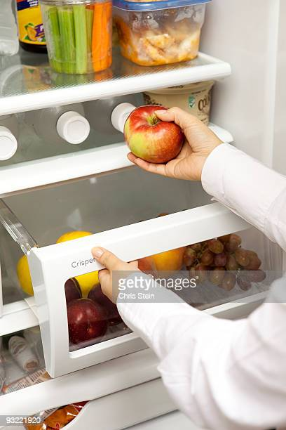 Woman taking a red apple out of a refrigerator