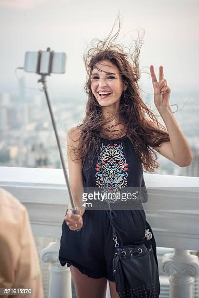 Femme prenant un Selfie avec un bras télescopique pour smartphone sur vacances