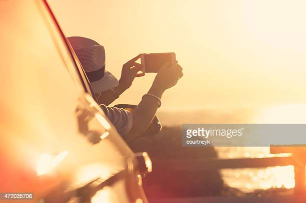 Femme prenant une photo du coucher de soleil dans une voiture.