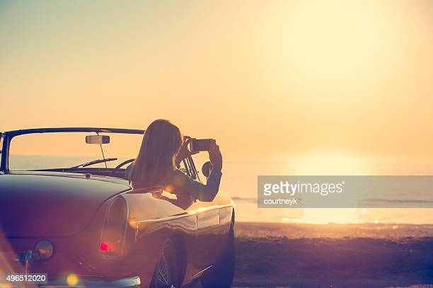 Woman taking a sunset photo in a convertible car.