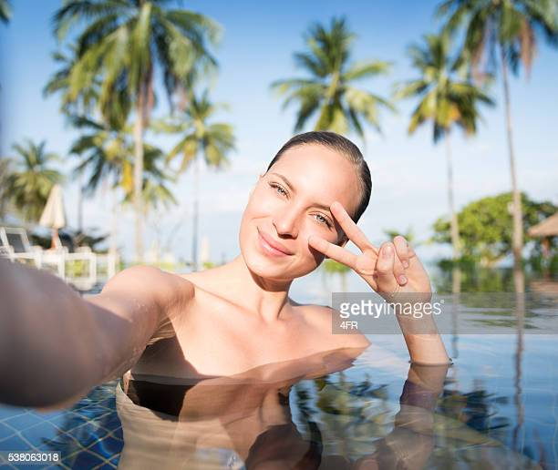 Woman taking a Vacation Selfie in the Pool
