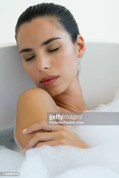 Woman taking bubble bath with eyes closed