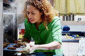 Woman taking burnt cookies from oven