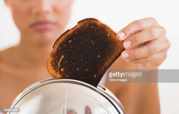 Woman taking burnt toast from toaster