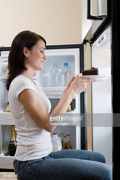 Woman taking cake out of refrigerator