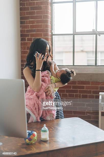 A woman taking care of a baby while talking on the phone