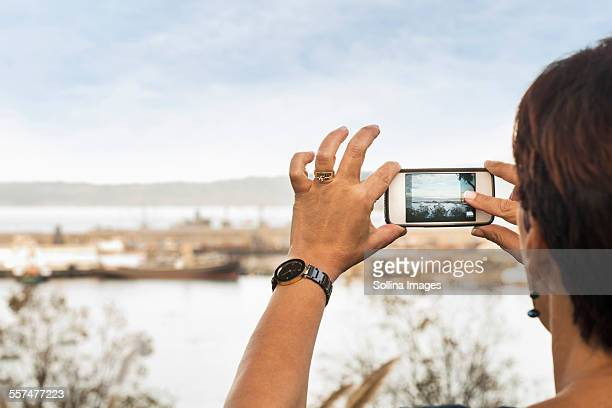 Woman taking cell phone photograph of beach