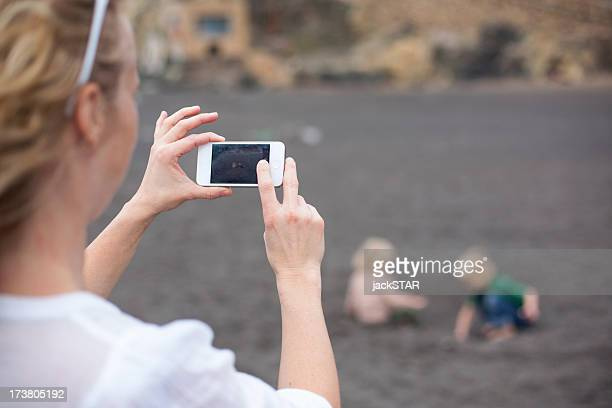 Woman taking cell phone picture on beach