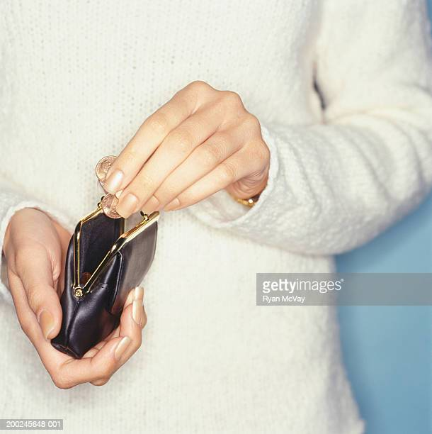 Woman taking coins from purse, Close-up of hands