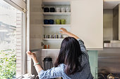 Woman taking cups out from shelf
