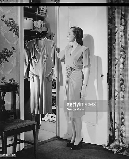 Woman taking dress from wardrobe, (B&W)