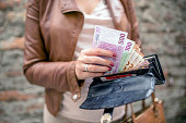 woman taking euro money from black wallet. City girl is taking out money from wallet. Woman hands holding European bank notes