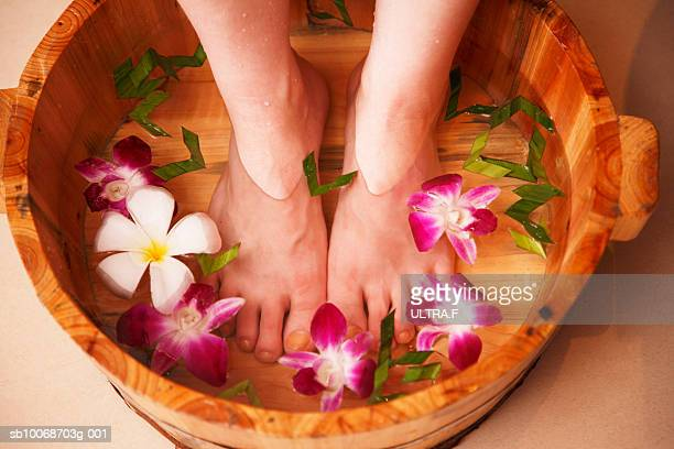Woman taking foot bath, low section