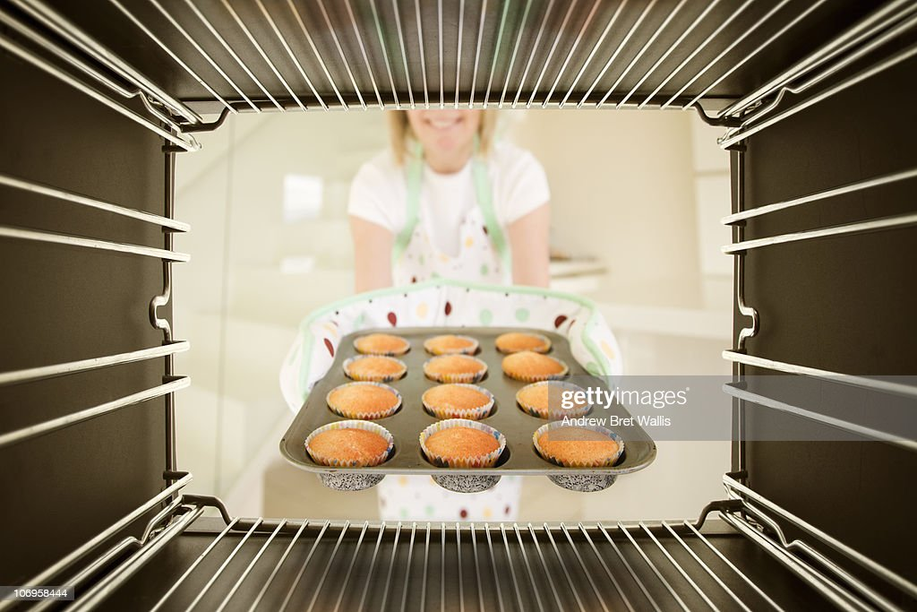 woman taking freshly baked buns out of an oven