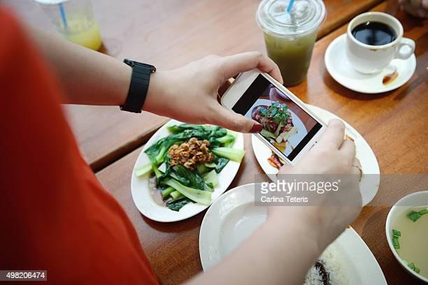 Woman taking handphone photo of food