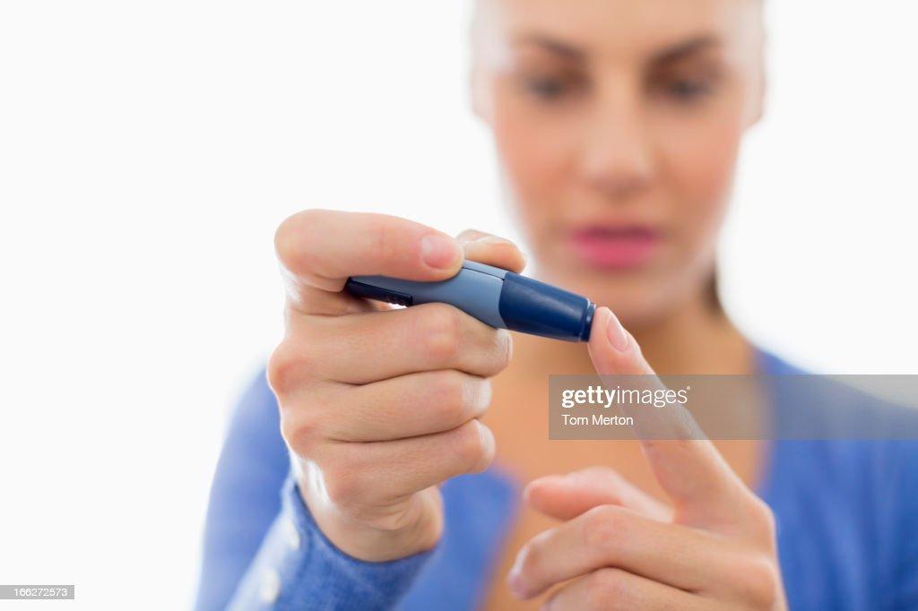 Woman taking her own blood sugar : Stock Photo