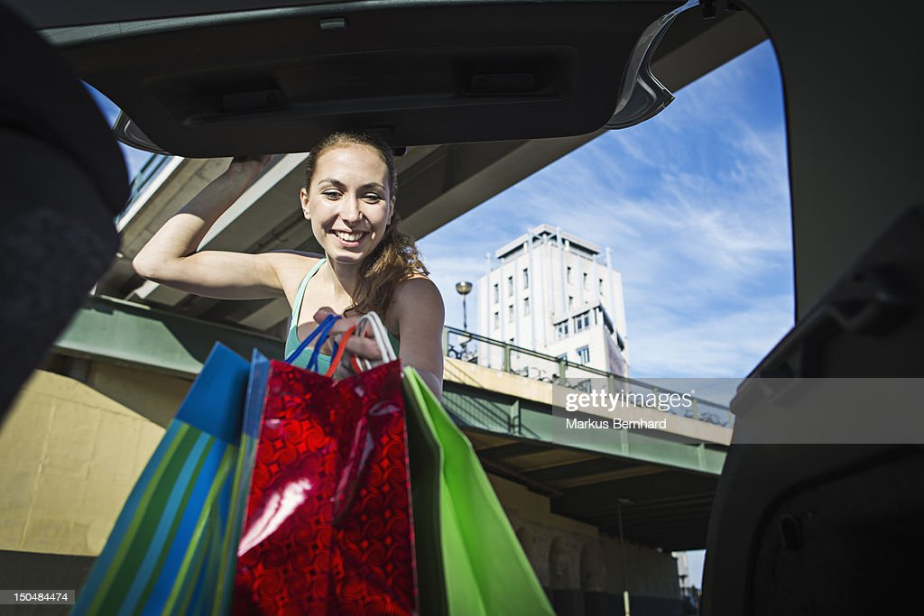 Woman taking her shopping out of the trunk. : Stock Photo