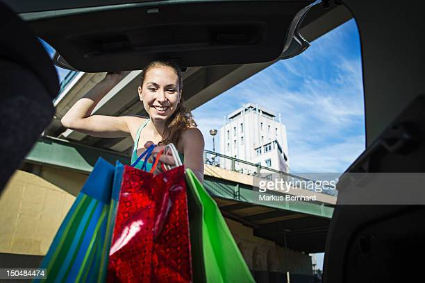 Woman taking her shopping out of the trunk.