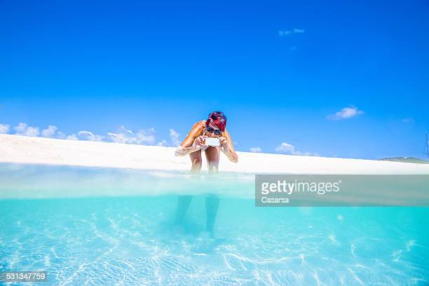 Woman taking images with her smarthone on beautiful beach
