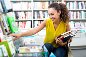 Beautiful glad woman taking literature books in store with prints