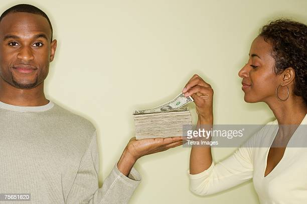 Woman taking money from stack in husband's hand