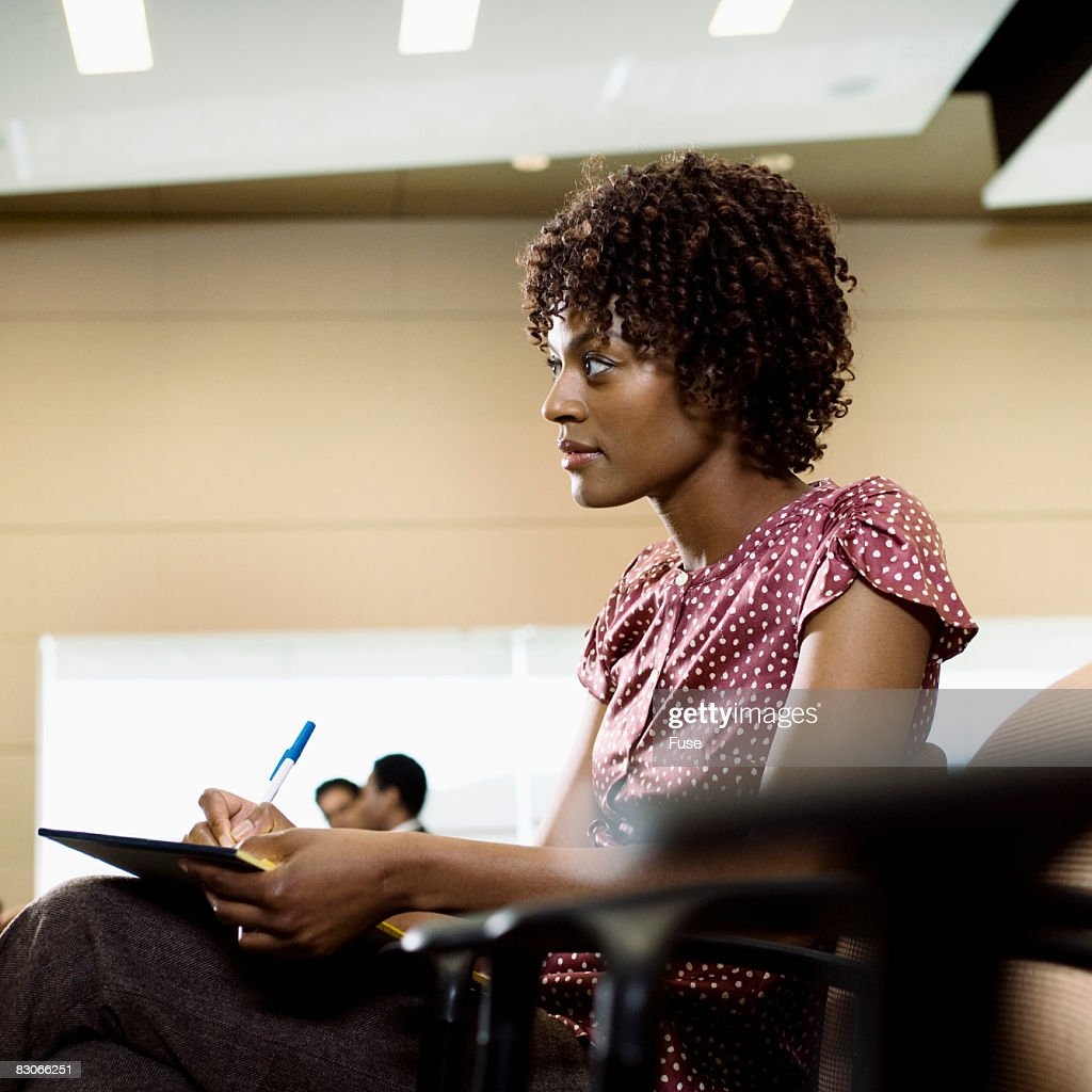 Woman Taking Notes in Meeting