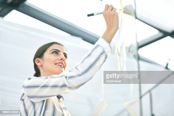 Woman taking notes on glass board