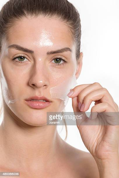 Woman taking off facial mask