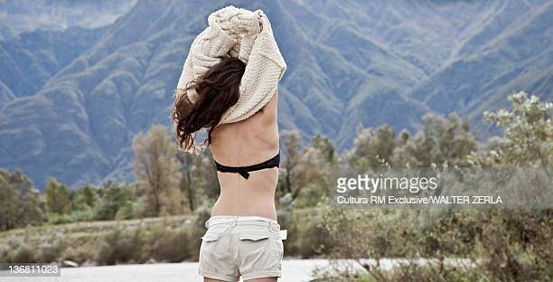 Woman taking off her sweater by lake
