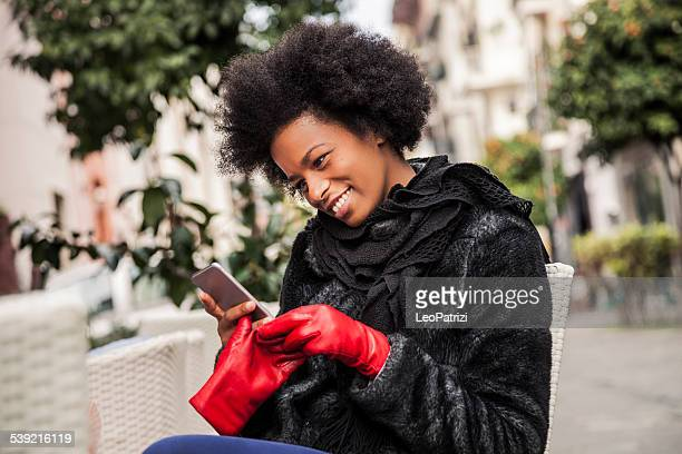 Woman taking off the gloves to write on the phone