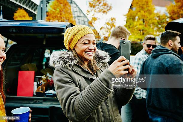 Woman taking photo during tailgating party