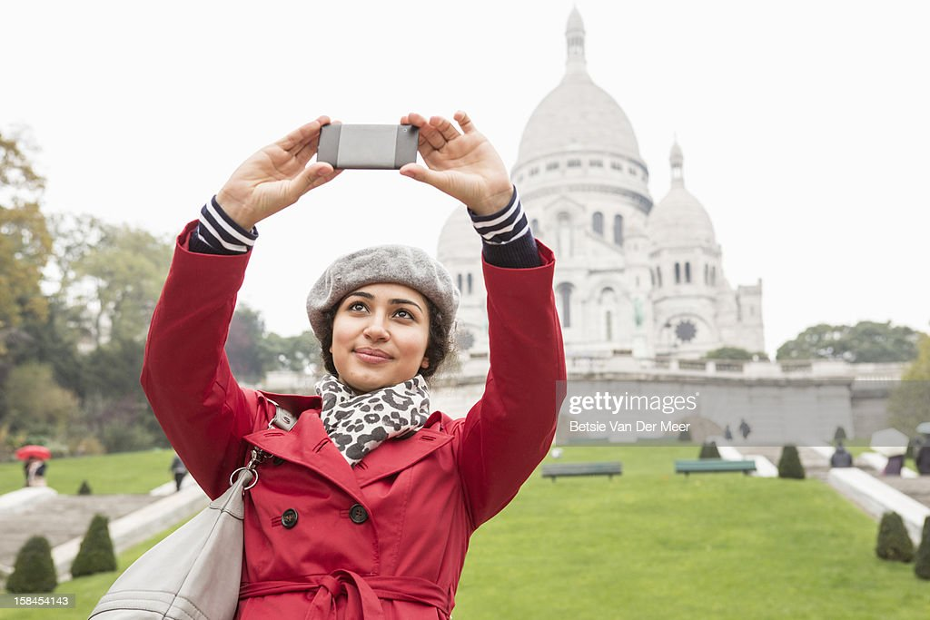 Woman taking photo in front of Sacre Coeur. : Stock Photo