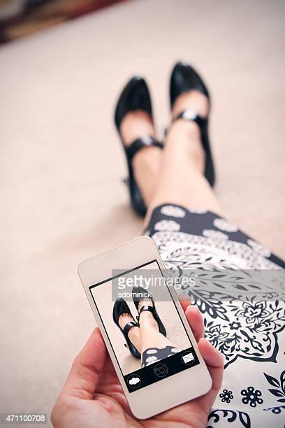 Frau nimmt Foto von Füße auf Smart Phone
