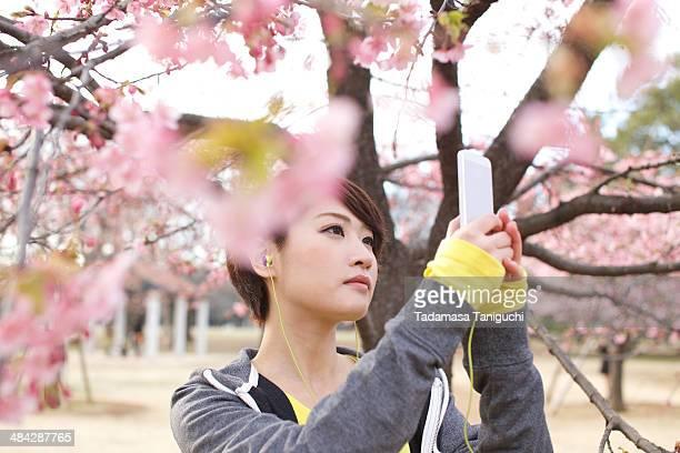 Woman taking photo of flower