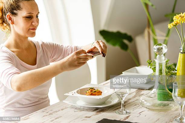 Woman taking photo of food with smartphone