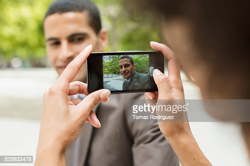 Woman taking photo of man with cell phone : Stockfoto