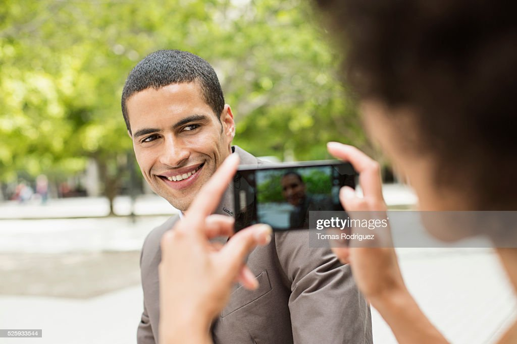 Woman taking photo of man with cell phone : Stock-Foto