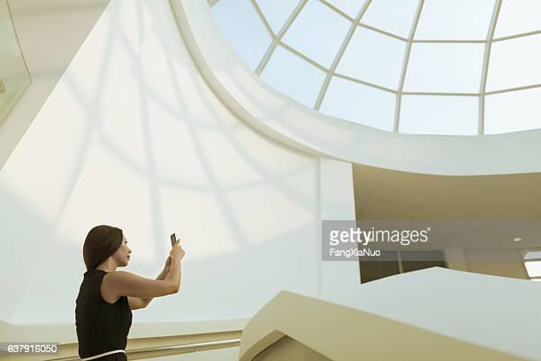 Woman taking photo of modern skylight in atrium