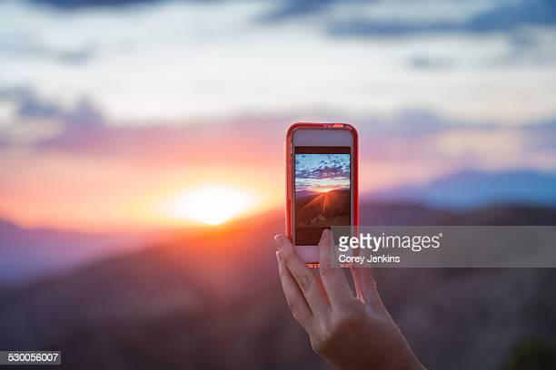 Woman taking photo of mountain, Joshua Tree National Park, California, US