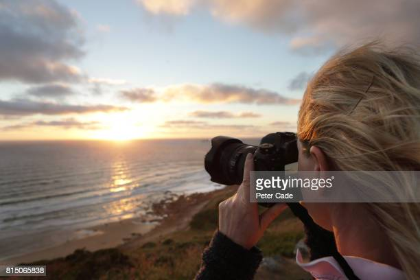Woman taking photo of sunset from clifftop
